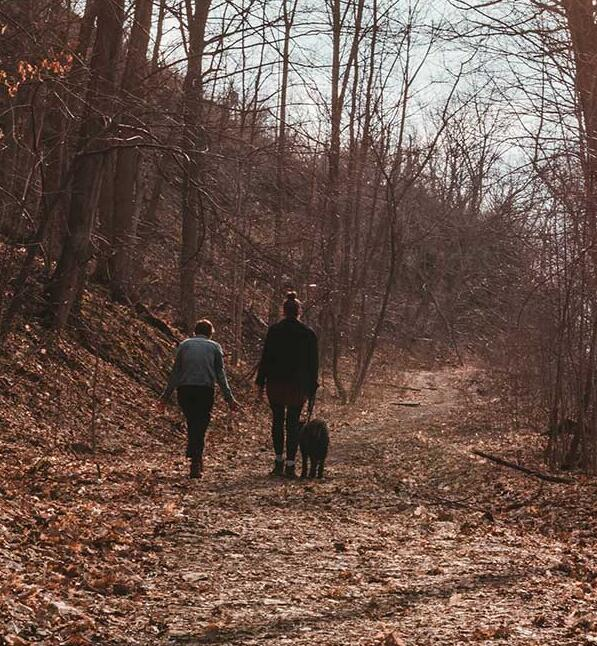 people-walking-a-dog-through-the-woods